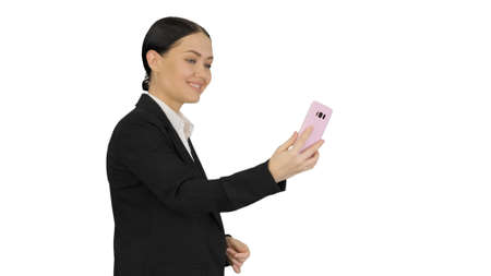 Young female in a suit having business video call on her phone o