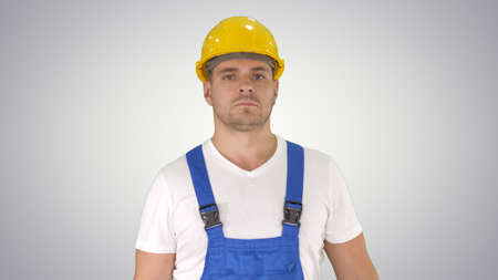 Builder walking and looking to camera on gradient background.