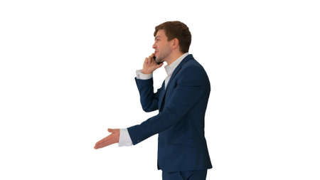 Stressed and angry businessman talking on the phone on white bac