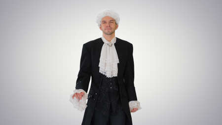 Man in old-fashioned laced frock coat and white wig walking in a Stock Photo