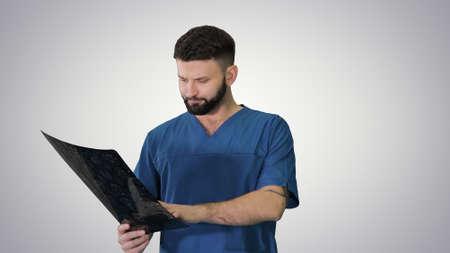 Surgeon studying mri brain scan while walking on gradient backgr