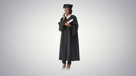 African American female student in graduation robe talking on th