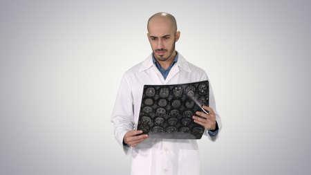 Arabian physician reviewing a MRI brain scan while walking on gr