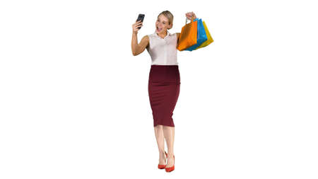 heerful woman with shopping bags taking selfie on white background. Imagens