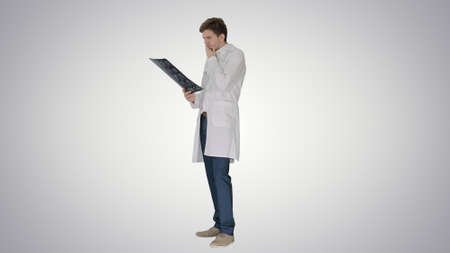Concentrated male doctor looking at computed tomography xray ima