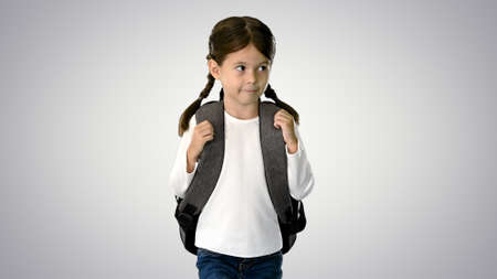 Smiling little girl walking to school holding her backpack and l