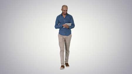 Arabian man walking and using tablet surfing internet on gradien