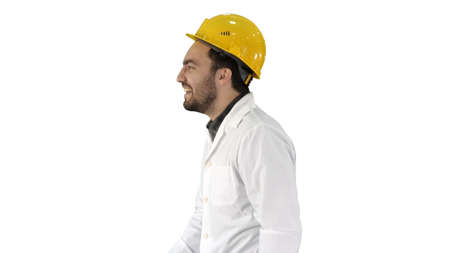 Smiling construction engineer catching a cap and putting it on o