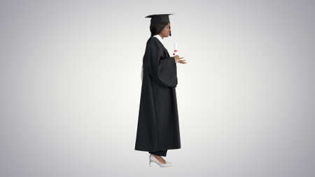 African American female graduate holding diploma and giving spee