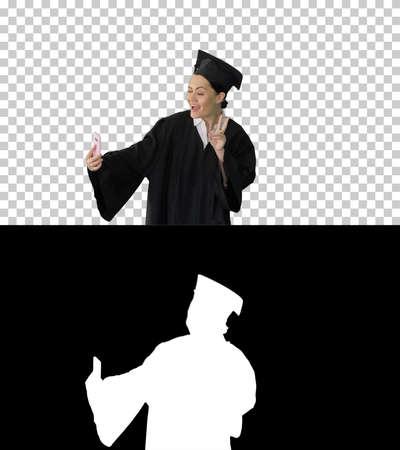 Happy female graduate in mortarboard making selfie on her phone,