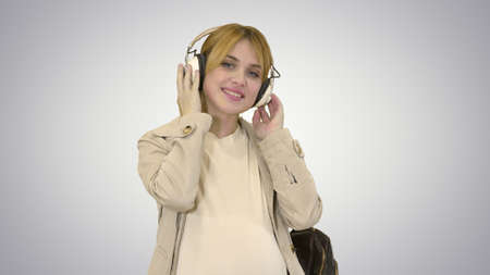 Young attractive pregnant woman listening to music in headphones on white background.