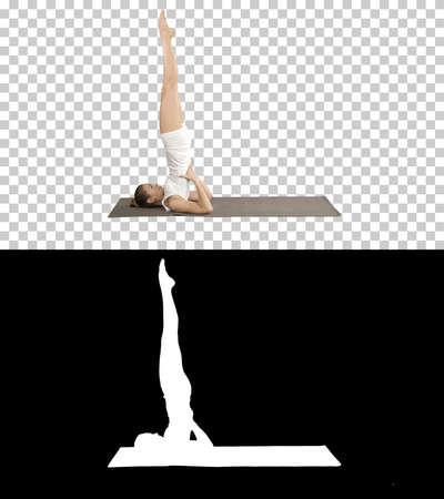 Woman practicing yoga, standing in salamba sarvangasana exercise