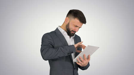 Turk business man with a beard standing and using tablet compute