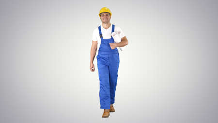 Construction worker walking with blue prints and smiling to came