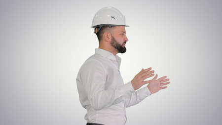 Male architect explaining something while walking on gradient ba
