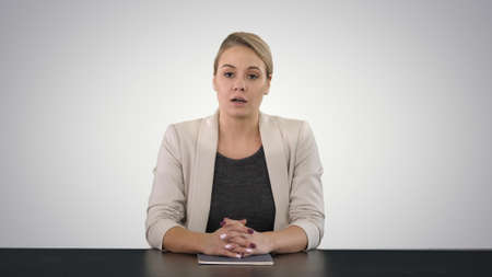 Young beautiful television announcer giving a speach on gradient background