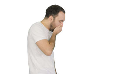 Sleepy male in white t-shirt yawning and rubbing eyes while walk