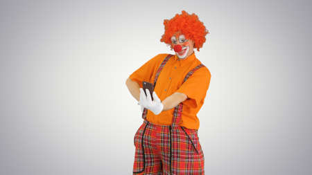 Clown taking selfie with his phone on gradient background.