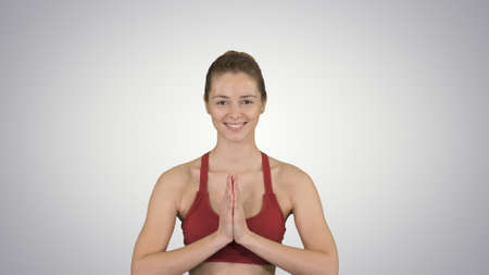 Yoga smiling woman with hands coupled on gradient background.