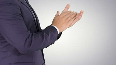 Business man clapping hands on gradient background.