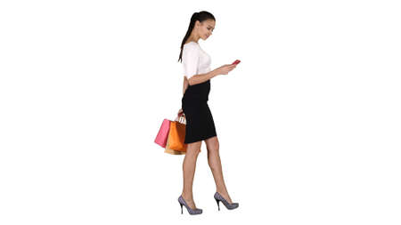 Beautiful young woman using a mobile phone walking and holding shopping bag