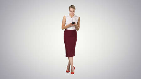 Attractive european female with smartphone in hand, touching screenphone