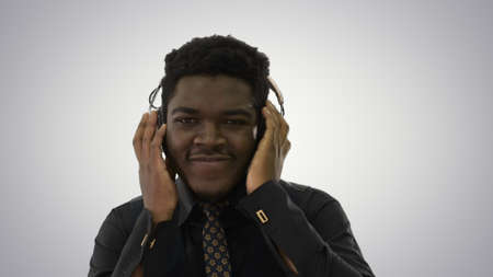 African american man holding headphones with both hands and groo