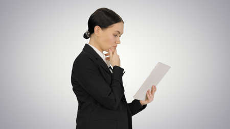 Businesswoman using a tablet pad while walking on gradient backg