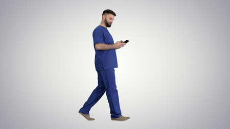 Surgeon doctor walking and using his phone on gradient backgroun