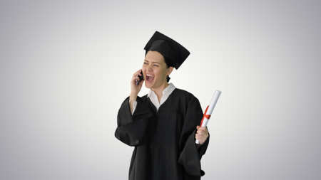 Happy female student in graduation robe talking emotionally on t Banque d'images