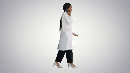 African american female doctor talking on the phone while walkin
