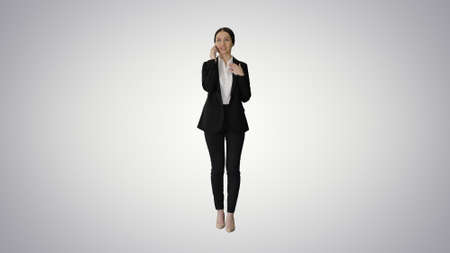 Young Businesswoman talking on her phone on gradient background. Banque d'images