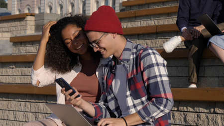Millennial man and woman explore social media together using sma