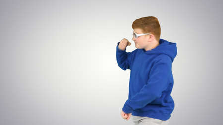 Cool boy dancing while walking by on gradient background. Banque d'images