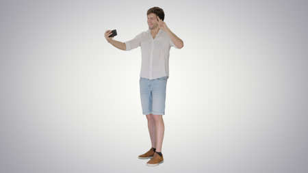 Young man in casual white shirt taking selfies on his phone on g Banque d'images