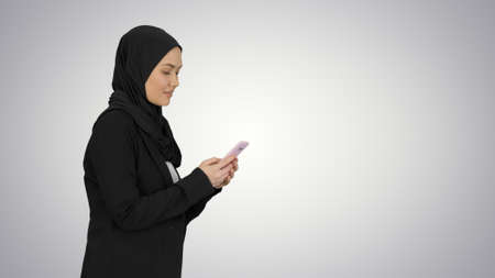 Muslim woman messaging on her mobile phone while walking on grad