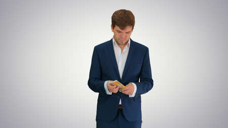 Happy businessman counting money and tucking it inside a jacket