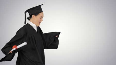 Happy female student in graduation robe walking and cheering wit