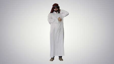 Cool sheikh in sunglasses posing on gradient background.