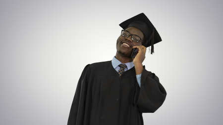 Smiling african american male student in graduation robe talking