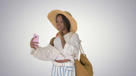 Smiling african american woman wearing straw hat and taking self