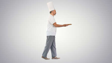 Cook walking in a hurry with a pizza in his hands on gradient ba