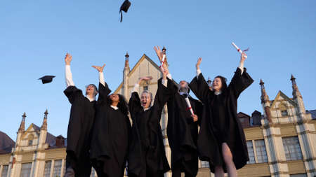 Group of diverse graduation students throwing their mortarboards