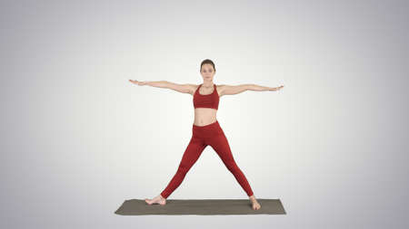 Woman practicing yoga, standing in Extended Side Angle exercise, 版權商用圖片