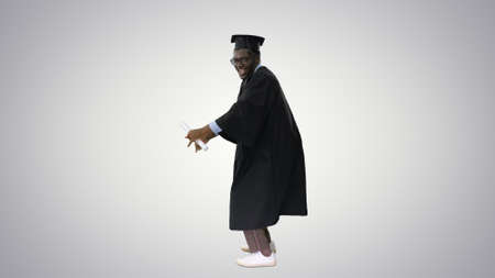 Excited african american male student in graduation robe dancing