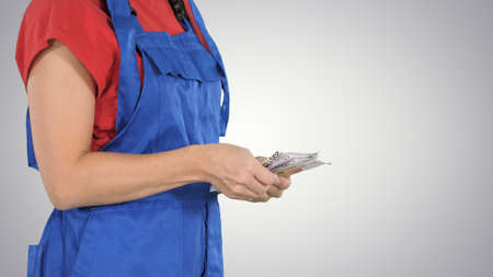 A woman in a workers clothes counts money on gradient background