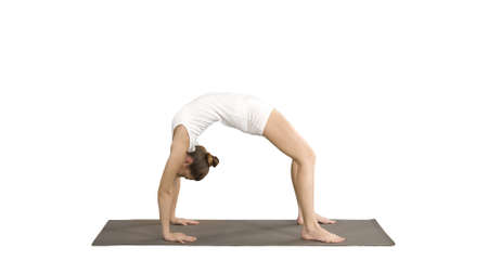 Sporty yoga girl performing Chakrasana Urdva Dhanurasana Wheel Pose on white background.