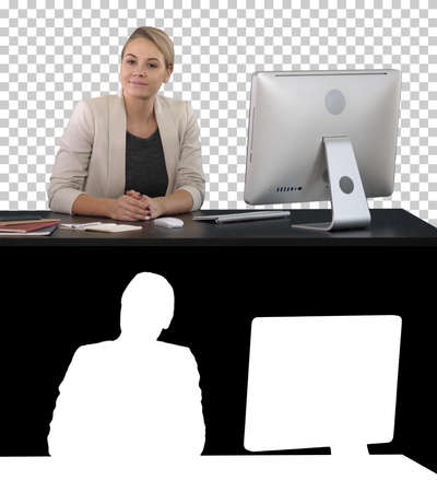 Cheerful businesswoman sitting at the table in office and lookin