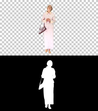 Smiling senior lady in glasses and with a handbag walking, Alpha 版權商用圖片