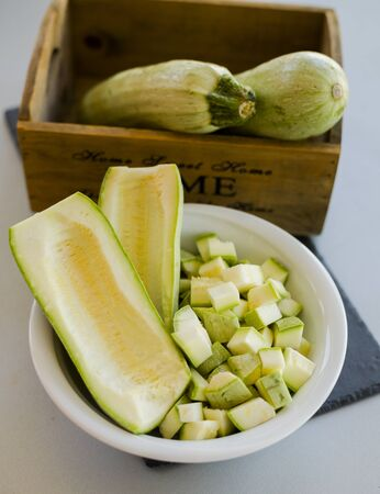 Bowl with cutted zuchini on stone slate on kitchen table, close-up